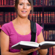 Smiling woman with a book in library — Stockfoto