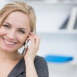 Smiling business woman using mobile phone in office — Stock Photo