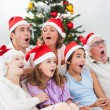 Stock Photo: Extended family singing carols