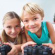 Happy siblings playing video games on floor — Stock Photo #24113669