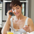 Woman eating breakfast and talking on phone - Stock Photo