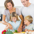 Mother teaching daughter to slice vegetables as father and son a - Stock Photo