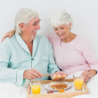 Smiling couple having breakfast in bed — Stock Photo