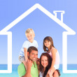 Family posing with a house illustration and the sea — Stock Photo