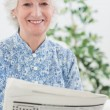 Stock Photo: Elderly smiling womreading newspapers
