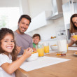 Family smiling at the camera at breakfast — Stock Photo #24115569