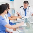Stock Photo: Meeting between doctor and three nurses