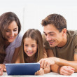 Family lying on a carpet with tablet — Stock Photo #24115773