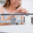 Woman adjusting scale — Stock Photo