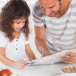 Stock Photo: Dad and daughter reading a newspaper