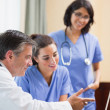 Doctor showing nurses something on laptop - Foto Stock