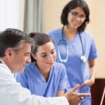 Doctor showing nurses something on laptop — Stock Photo