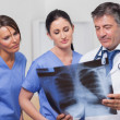 Doctor and nurses looking x-ray — Stock Photo #24116281