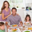 Family smiling at the dinner table — Stockfoto