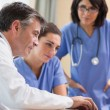 Stock Photo: Doctor and two nurses looking at laptop