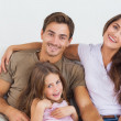 Happy family sitting together on a sofa - Stockfoto