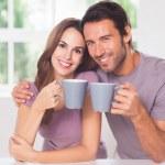paar kijken naar de camera met een kopje koffie — Stockfoto