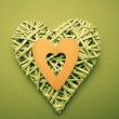 Wicker heart ornament with yellow paper cut out — Stock Photo