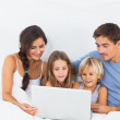 Family sitting with a laptop — Stock Photo #24116407