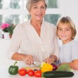 Stockfoto: Grandmother cutting vegetables with her grandson