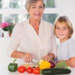grootmoeder snijden groenten met haar kleinzoon — Stockfoto