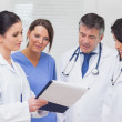 Nurse and doctors looking at clipboard — Stock Photo