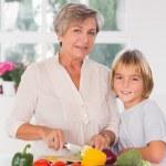 oma snijden groenten met haar kleinzoon — Stockfoto