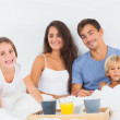 Happy family taking the breakfast on the bed — Stock Photo