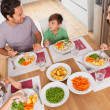 Family smiling around a healthy meal — Stock Photo