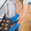 Mother and her daughter taking cookies from the oven — Stock Photo