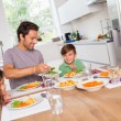 Father serving vegetables to son — Stock Photo