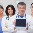 Doctor showing tablet pc with his team — Stock Photo