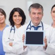 Stock Photo: Doctor showing tablet pc with his team