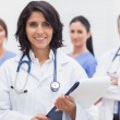 Female doctor with clipboard and her team smiling — Stock fotografie