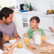 Family laughing around breakfast - Stockfoto
