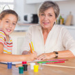 Child with her grandmother looking at the camera while drawing — Stock Photo