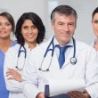 Doctor holding clipboard with his team — Stock Photo