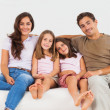 Cute family sitting on a sofa - Stock Photo