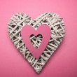 Wicker heart ornament with pink paper cut out — Stock Photo #24116913