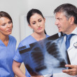 Stock Photo: Doctor speaking about x-ray with nurses