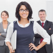 Smiling businesswoman and her team - Stock Photo