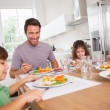 Family smiling around a good meal — Stockfoto