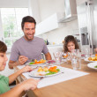 Stock Photo: Family smiling around a good meal