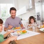 Семья, улыбаясь вокруг хорошей едой — Стоковое фото