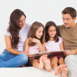 Family reading a story on a sofa — Stock Photo