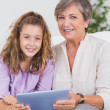 Child and her grandmother looking at the camera with tablet pc — Stock Photo