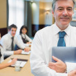 Businessman holding digital tablet at meeting — Stock Photo