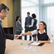 Stock Photo: Womhanding name tag to businessman