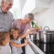 Stock Photo: Children cooking with grandparents