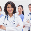 Female doctor and her team smiling - Stock Photo
